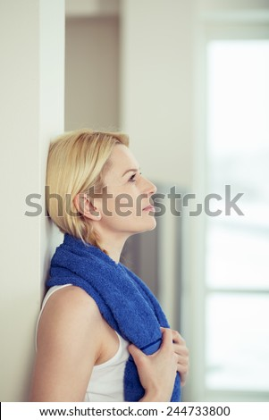 Fit young woman standing thinking as she relaxes after a workout in the gym leaning against a wall with a towel around her neck staring into the air, upper body profile view - stock photo