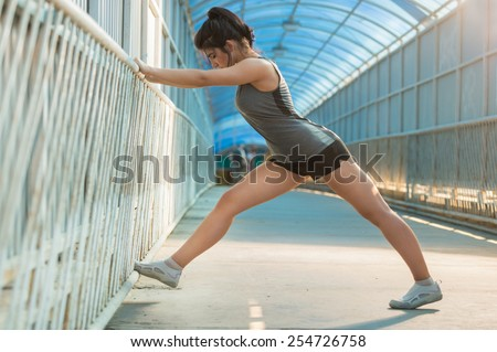 Fit young woman stretching before a run. Young female runner stretching her muscles before a training session - stock photo