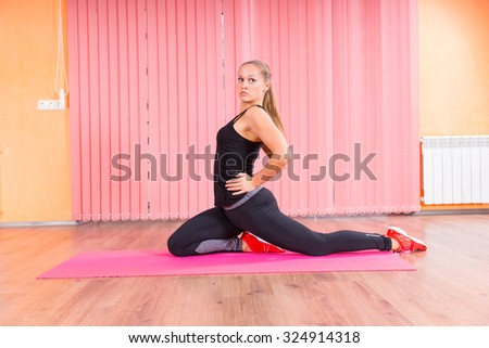 Fit Young Woman Stretching her Back and Leg on Top of a Pink Fitness Mat Inside the Studio. - stock photo