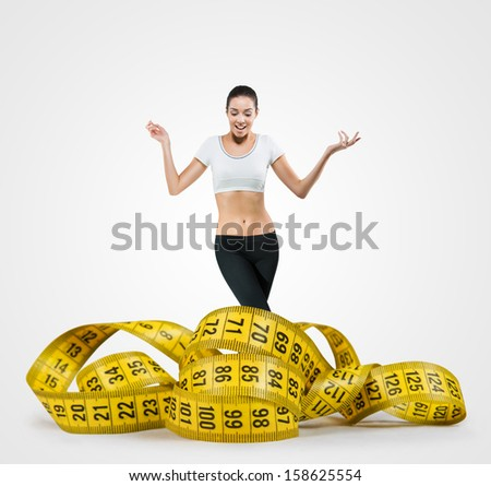 Fit young woman with a large measuring tape - stock photo