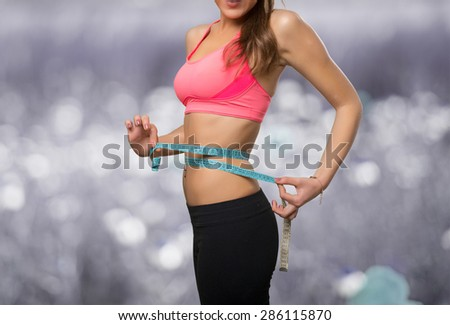 Fit young woman with a measurement scale. Over abstract background - stock photo