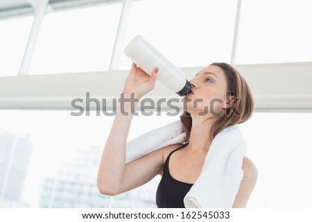 Fit young woman with towel around neck drinking water in bright fitness studio