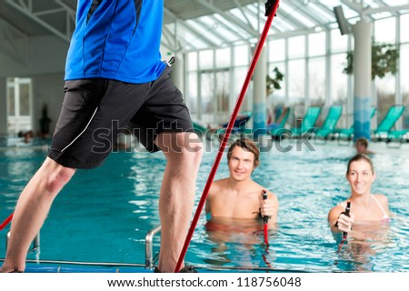 Fitness - a young couple - man and woman - doing sports and gymnastics or water aerobics under water in swimming pool or spa with Nordic walking sticks and trainer