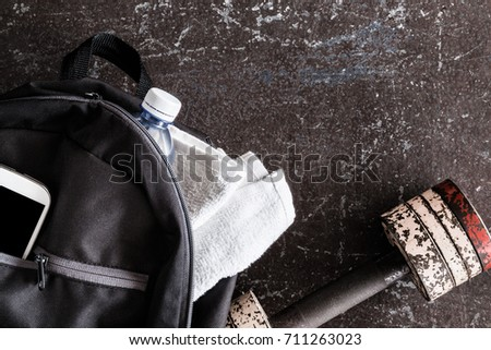 Fitness accessories on the dark floor in the gym. Dumbbell, black sport bag, smart phone, towels, water bottle. Cares about a body. Sport concept. Top view.