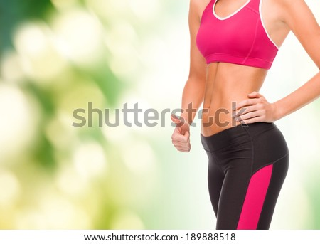 fitness and diet concept - close up of female abs and hand showing thumbs up - stock photo