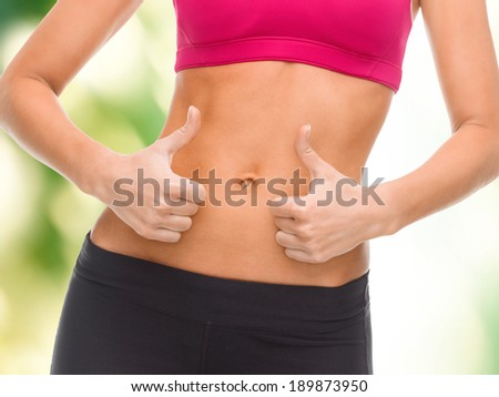 fitness and diet concept - close up of female abs and hands showing thumbs up - stock photo