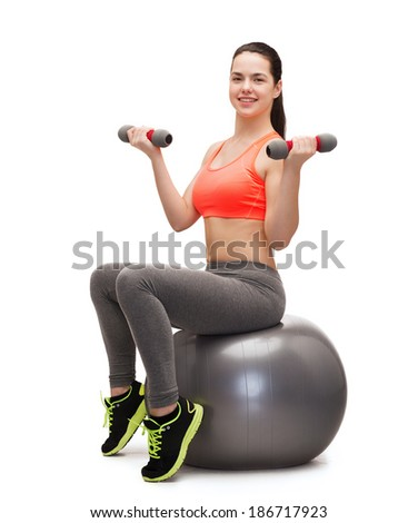 fitness and diet concept - smiling teenage girl with dumbbells sitting on fitness ball