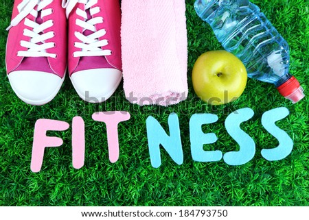 Fitness and healthy life. Conceptual photo. Gumshoes, towel, dumbbells and water bottle on green grass background - stock photo