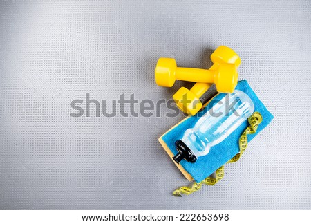 Fitness and healthy life. Conceptual photo Various accessories for sports training, water bottle, towel, measuring tape - stock photo