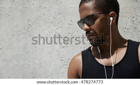 Fitness and healthy lifestyle concept. Dark-skinned athlete resting after hard workout. Black runner in trendy shades and black A-shirt looking down, listening to meditative sounds with earphones