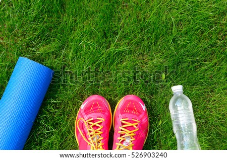Fitness and healthy lifestyle concept, sport shoes, bottle of water and mat on grass background