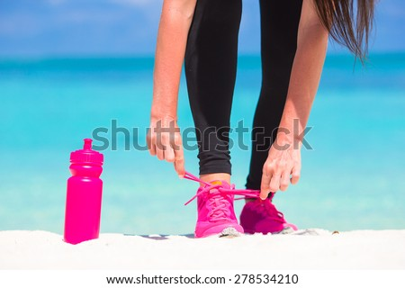 Fitness and healthy lifestyle concept with female model tying laces on sneakers - stock photo