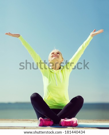 fitness and lifestyle concept - woman doing yoga outdoors - stock photo