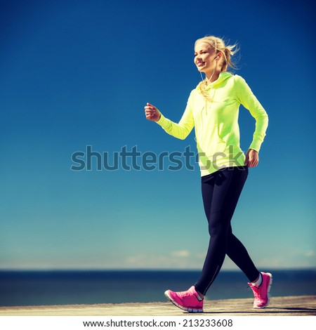 fitness and lifestyle concept - woman walking outdoors - stock photo