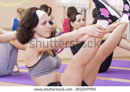 Fitness and Pilates Concepts. Group of  Caucasian Female Athletes Stretching Legs Muscles on Sport Mats. Horizontal Image - stock photo