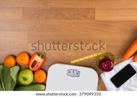 Fitness and weight loss concept, dumbbells, white scale, fruit and tape measure on a wooden table, top view, free copy space - stock photo