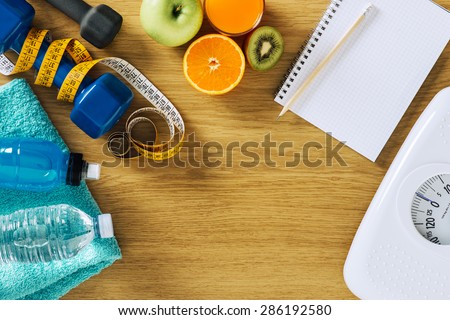 Fitness and weight loss concept, dumbbells, white scale, notebook, tape measure and fruit on a wooden table, top view - stock photo