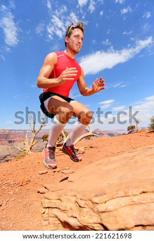 Fitness athlete bench jump squat jumping in nature landscape. Strength training fit male working out exercising outdoors in summer doing jumping on rock. - stock photo