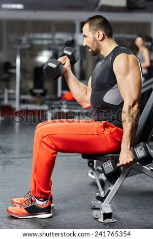 Fitness athlete doing biceps workout with dumbbell in a gym