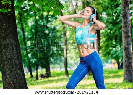 Fitness athlete runner with headphones running in park and listening to music. - stock photo