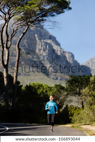 Fitness athlete training alone on a mountain road. Running endurance marathon woman exercising for healthy lifestyle and wellness. panorama with copyspace XXL - stock photo