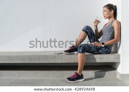 Fitness athlete woman drinking water during cardio workout break Healthy living hydration concept. Runner woman preventing dehydration for her health and body by hydrating on summer outdoors training. - stock photo