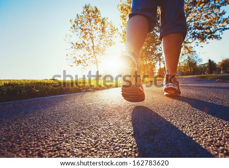fitness background, close up of runner feet on the road  - stock photo