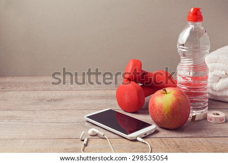 Fitness background with bottle of water, apple and smartphone - stock photo