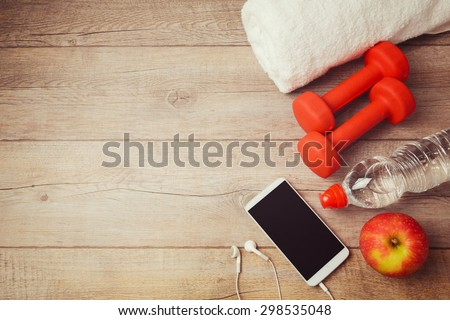 Fitness background with bottle of water, dumbbells and smartphone. View from above - stock photo