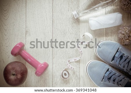 Fitness background with bottle of water, dumbbells and sneakers. View from above, Vintage Style. - stock photo