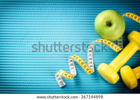 Fitness background with dumbbells, measuring tape and apple. Healthy lifestyle concept with copy space - stock photo