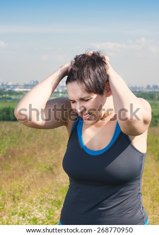 Fitness beautiful plus size woman with pain in her head outdoor - stock photo