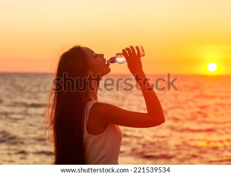Fitness beautiful woman drinking water and sweating after exercising on summer hot day in beach. Sunset. - stock photo