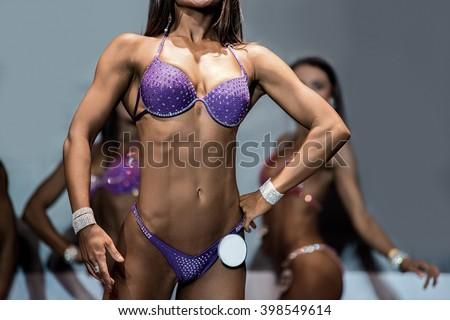 Fitness bikini athlete's lean torso. Woman demonstrating fit torso. Beautiful figure and tanned skin. Perfect female body. - stock photo