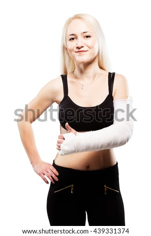 Fitness blond girl with a broken arm in plaster, making thumbs up gesture
