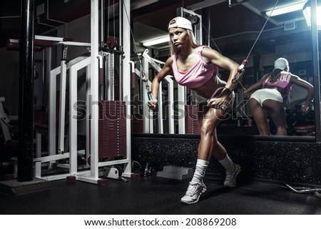 fitness blonde sexy girl exercising on block simulator in the gym