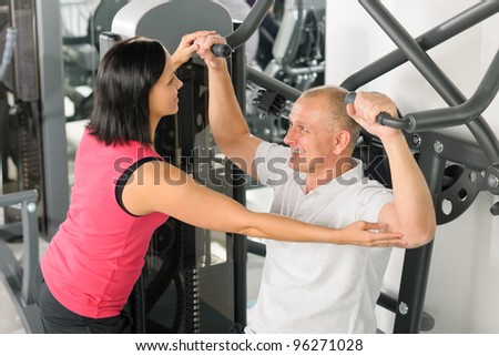 Fitness center personal trainer assist man exercise shoulder on machine - stock photo