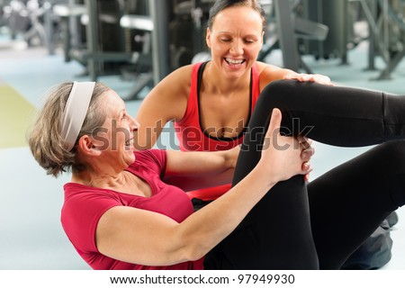 Fitness center senior woman exercise sit ups with personal trainer - stock photo