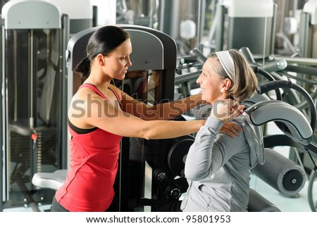 Fitness center senior woman exercise with personal trainer on machine