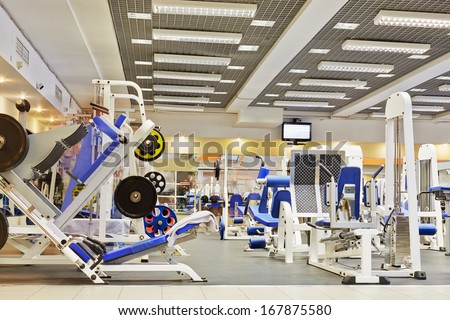 Fitness center with traineger equipments - stock photo
