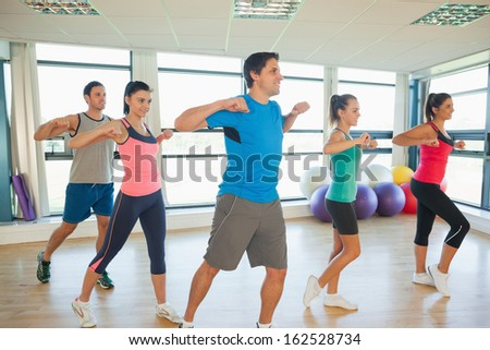 Fitness class and instructor doing pilates exercise in bright room - stock photo