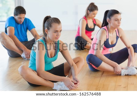 Fitness class and instructor doing the butterfly stretch in bright exercise room - stock photo