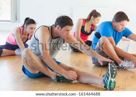 Fitness class and instructor stretching legs in bright exercise room - stock photo