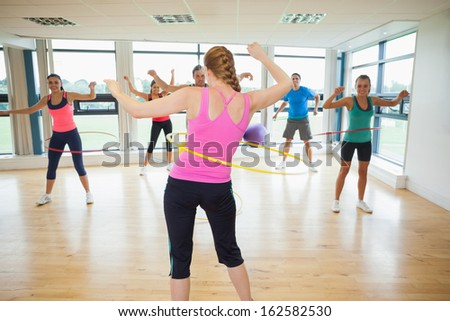 Fitness class and instructor swinging hula hoops at the waist in bright room - stock photo