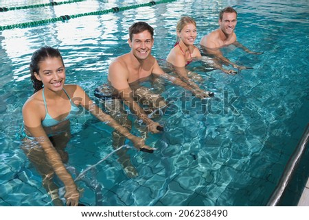 Fitness class doing aqua aerobics on exercise bikes in swimming pool at the leisure centre - stock photo