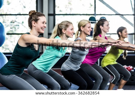 Fitness class doing exercises in the gym - stock photo