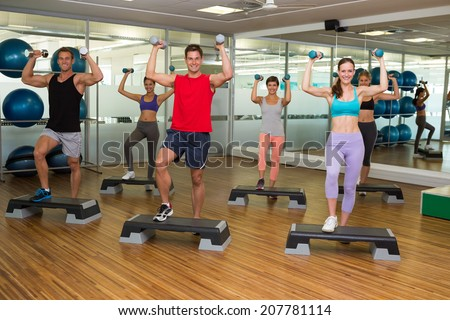 Fitness class doing step aerobics with dumbbells at the gym - stock photo