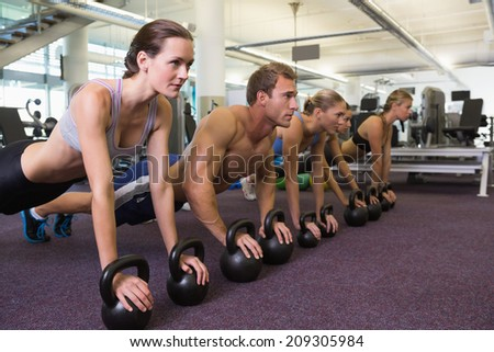 Fitness class in plank position with kettlebells at the gym - stock photo