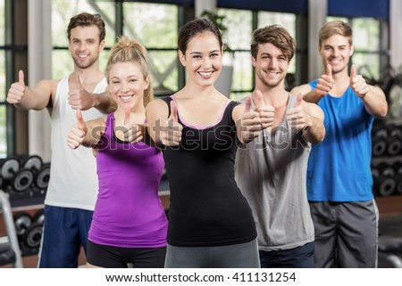 Fitness class showing thumbs up in gym - stock photo