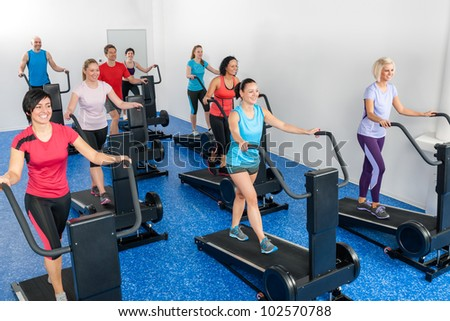 Fitness class walking on treadmill running deck at health club - stock photo
